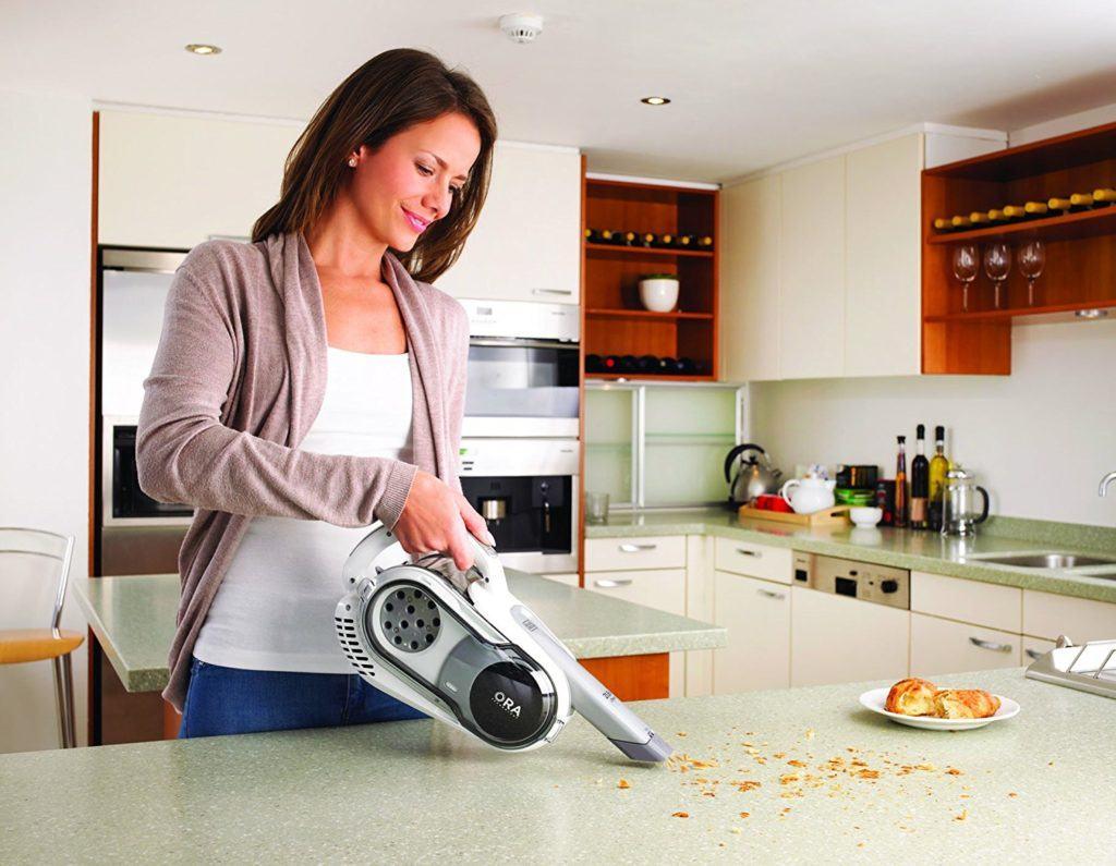 Frau saugt mit dem Black+Decker Handstaubsauger in der Küche im Staubsauger Test